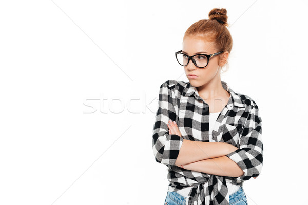 Serious ginger woman in eyeglasses posing with crossed arms Stock photo © deandrobot