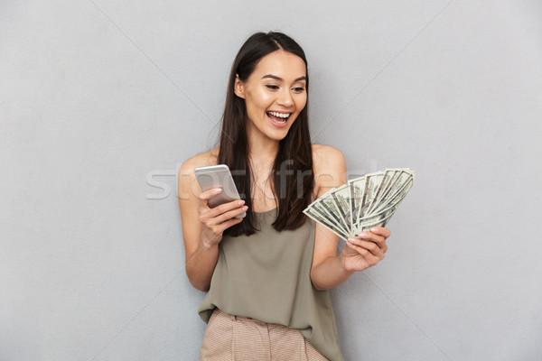 Portré derűs ázsiai nő tart pénz Stock fotó © deandrobot