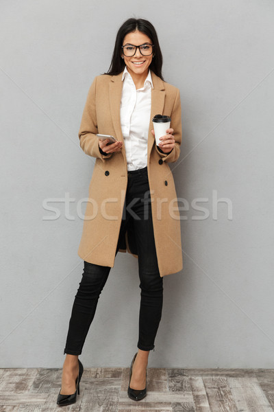 Full length image of beautiful woman wearing outerwear standing  Stock photo © deandrobot