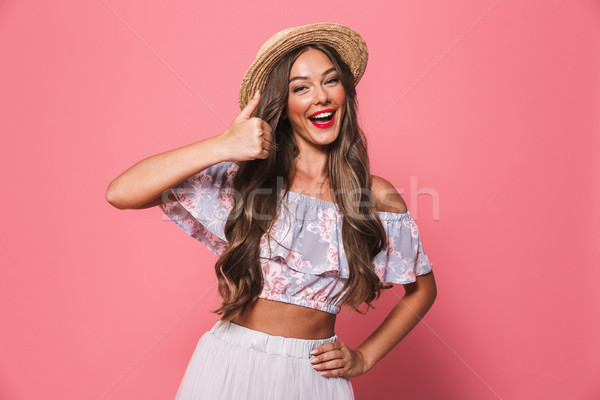 Portrait of happy brunette woman 20s wearing straw hat laughing  Stock photo © deandrobot