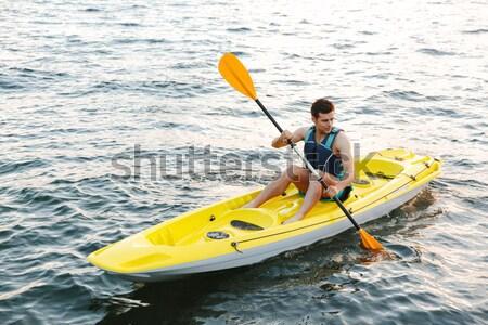 Man kajak zonsondergang water sport zee Stockfoto © deandrobot
