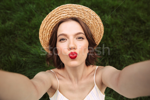 Pleased woman in dress and straw hat making selfie Stock photo © deandrobot