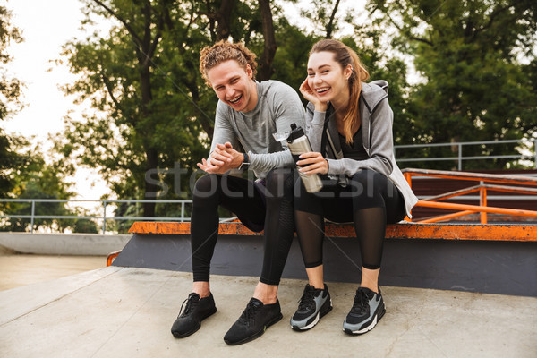 Photo of caucasian athletic couple guy and girl 20s in tracksuit Stock photo © deandrobot