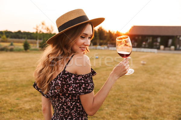 Pretty young woman outdoors holding glass drinking wine. Stock photo © deandrobot