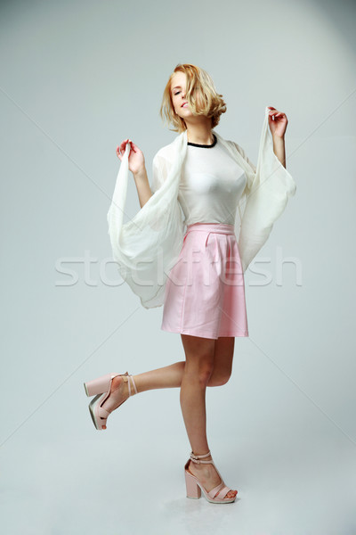 Studio shot of a young beautiful woman on gray background Stock photo © deandrobot