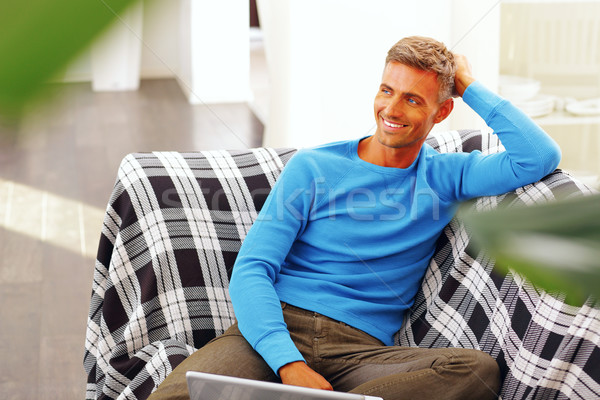 Handsome young man using laptop at home, sitting in armchair, smiling. Stock photo © deandrobot
