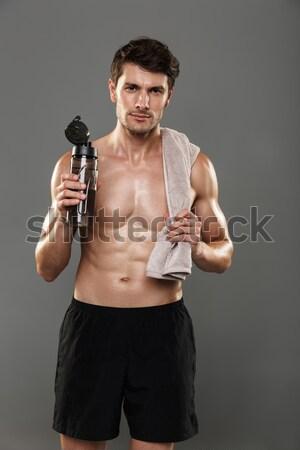Side view portrait of a sportsman lifting dumbbells over black background Stock photo © deandrobot