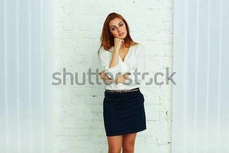 Cheerful businesswoman leaning at the wall in office Stock photo © deandrobot