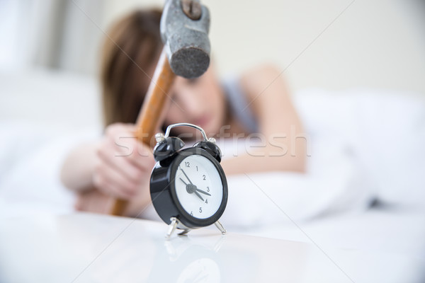 Woman not wanting to get up, taking a hammer to her alarm clock. Focus on clock Stock photo © deandrobot
