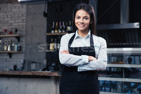 Happy pretty female waiter in apron Stock photo © deandrobot