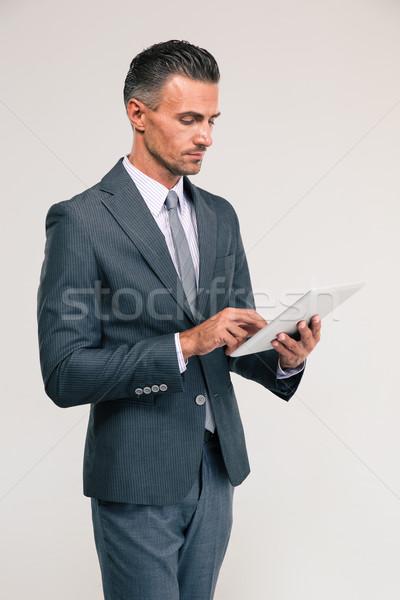 Handsome businessman using tablet computer Stock photo © deandrobot