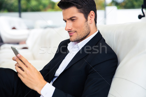 Handsome man using smartphone Stock photo © deandrobot