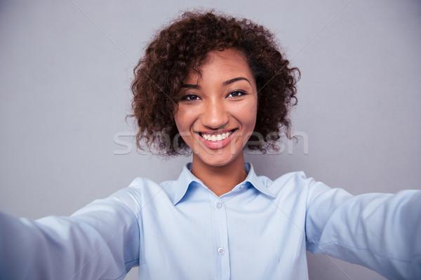 Happy afro american woman making selfie photo Stock photo © deandrobot