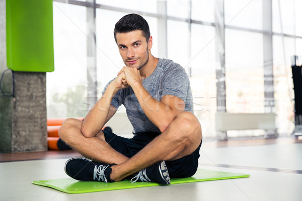 Fitness man sitting on yoga mat at gym Stock photo © deandrobot