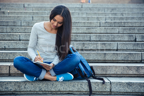 Happy female student writing notes in notepad  Stock photo © deandrobot