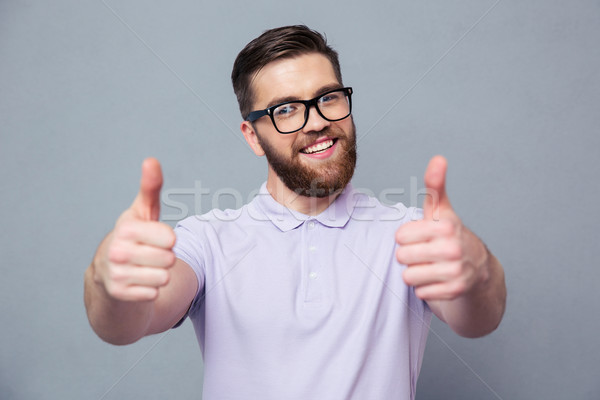 Casual man in glasses showing thumb up  Stock photo © deandrobot