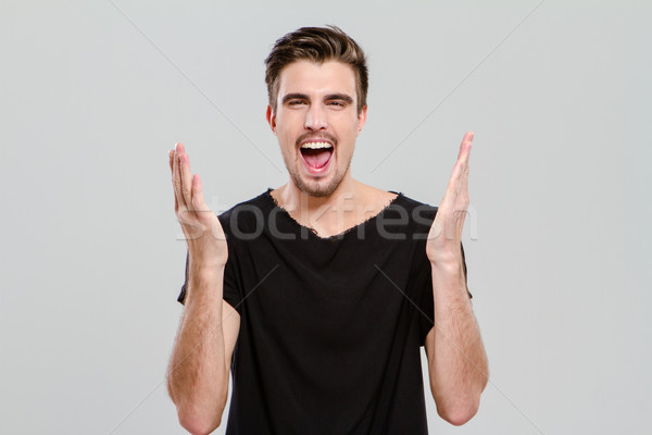 Portrait of young man screaming with hands up Stock photo © deandrobot