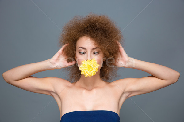 Amusing curly girl with flower in mouth kidding and squinting Stock photo © deandrobot