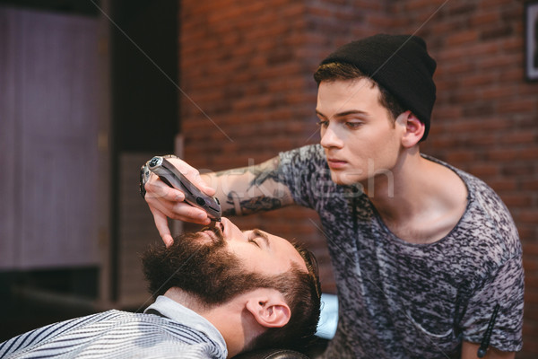 Concentrated barber trimming beard of handsome man in barbershop Stock photo © deandrobot