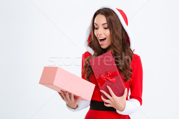 Surprised female in santa claus costume looking inside present box  Stock photo © deandrobot
