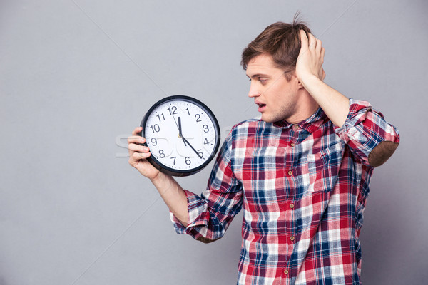 Worried man in checkered shirt holding and looking at clock Stock photo © deandrobot