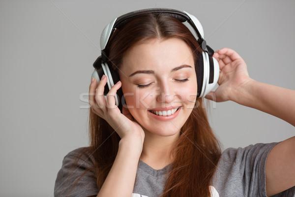 Glimlachend jonge vrouw luisteren naar muziek hoofdtelefoon grijs vrouw Stockfoto © deandrobot