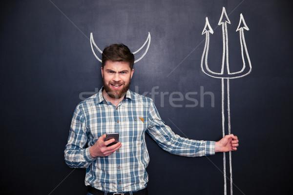 Bebaarde man smartphone permanente Blackboard jonge man Stockfoto © deandrobot