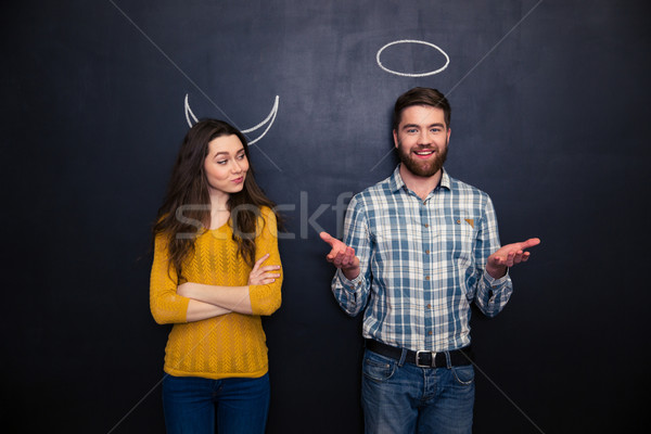 Happy couple playing devil and angel over blackboard background Stock photo © deandrobot