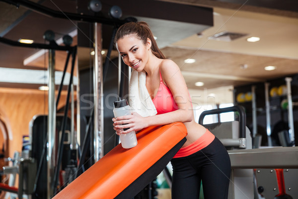 Happy sportswoman with bottle of water on training in gym  Stock photo © deandrobot