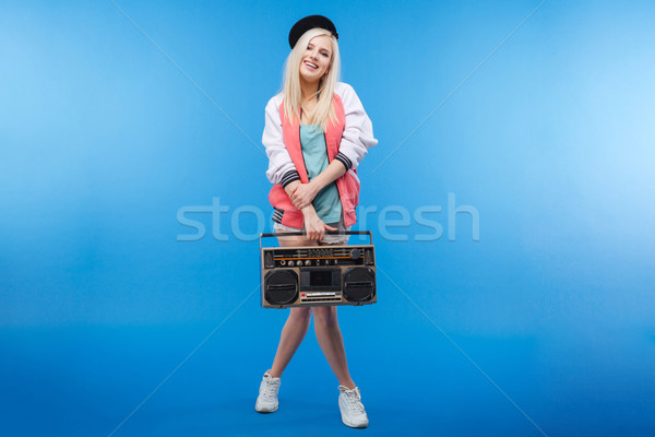 Happy female teenager holding retro boom box Stock photo © deandrobot
