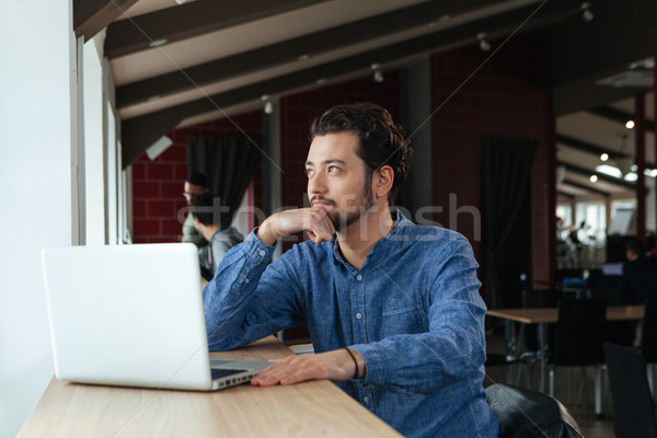 Pensive man sitting at the table with laptop Stock photo © deandrobot