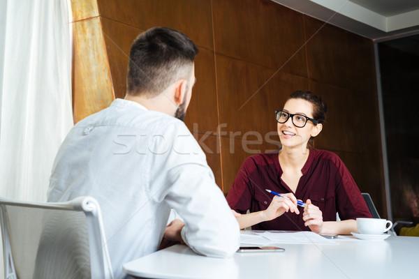 Mosolyog üzletasszony beszél fiatal üzletember tárgyalóterem Stock fotó © deandrobot