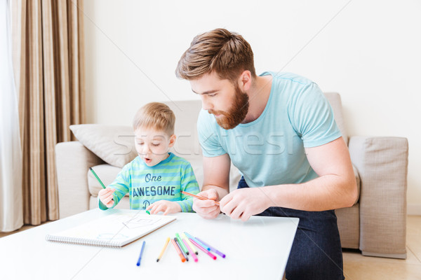 Stock photo: Father and son drawing in living room at home