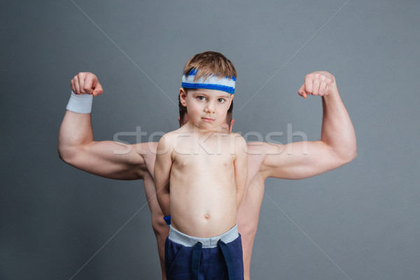 Father hiding behind his little son and showing biceps Stock photo © deandrobot