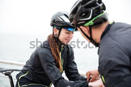 Kettő biciklisták pihen tenger férfi okostelefon Stock fotó © deandrobot