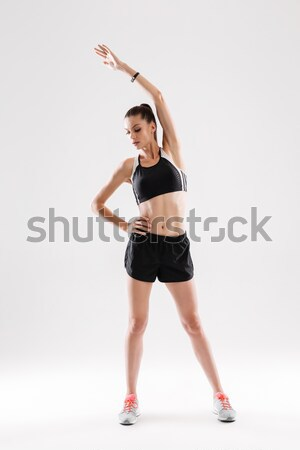 Young beautiful girl doing yoga posing over a grey background Stock photo © deandrobot
