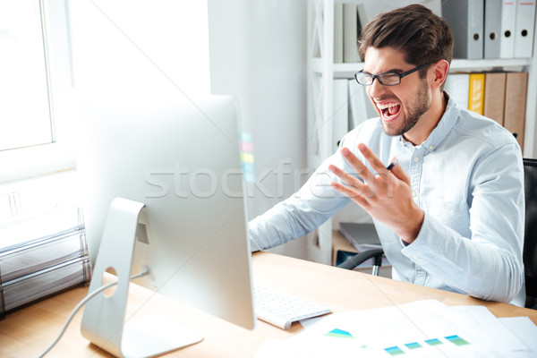 Angry mad young businessman working with computer and shouting Stock photo © deandrobot