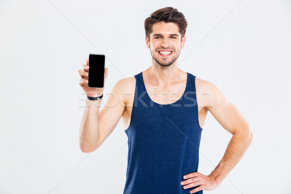 Cheerful young sportsman standing and holding blank screen mobile phone Stock photo © deandrobot
