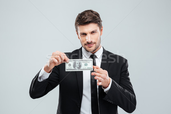 Attractive young businessman holding one hundred dollars banknote Stock photo © deandrobot
