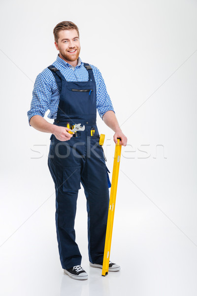 Happy male builder standing with equipment Stock photo © deandrobot
