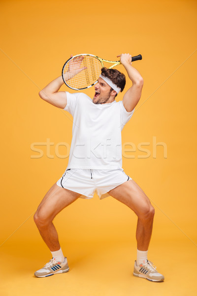Amusing young man tennis player holding racket and having fun Stock photo © deandrobot