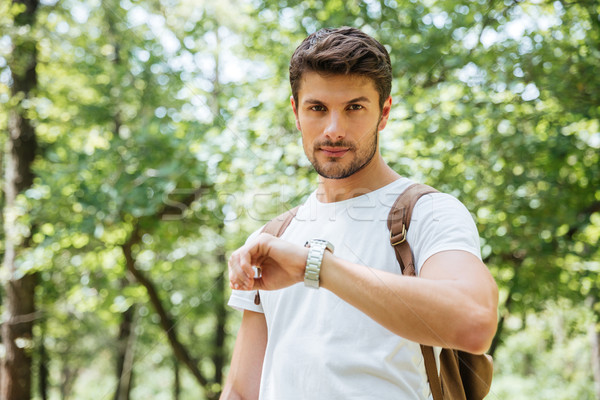 Serious man with backpack checking time and looking at watch Stock photo © deandrobot