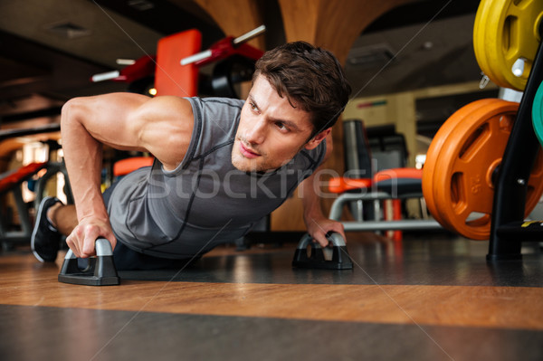Sportsman doing push-up exercises in gym Stock photo © deandrobot