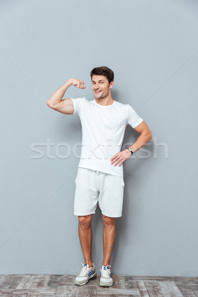 Full length of happy athletic man standing and showing biceps Stock photo © deandrobot