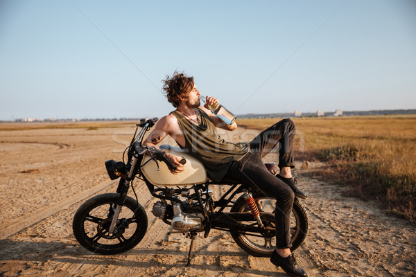 Young brutal man laying on his motorcycle and drinking water Stock photo © deandrobot