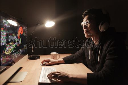 Smiling male gamer playing computer game in dark office Stock photo © deandrobot