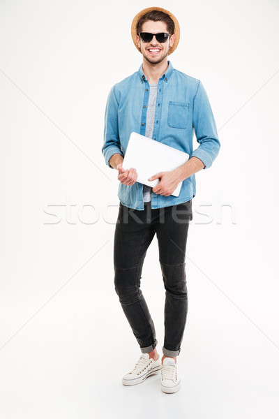 Stock photo: Happy young man in hat and sunglasses holding laptop