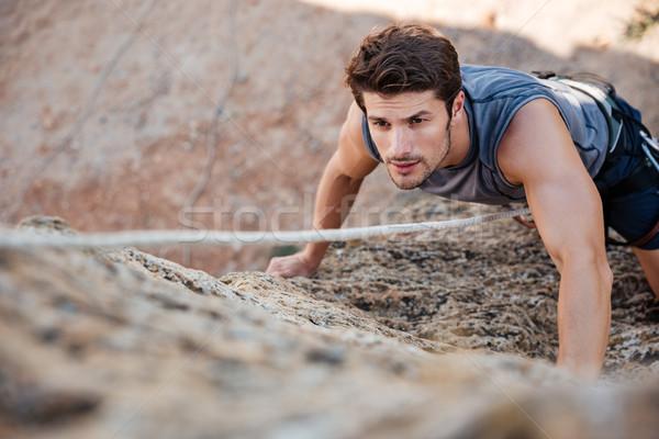 Férfi markolás kő meredek szirt fal Stock fotó © deandrobot
