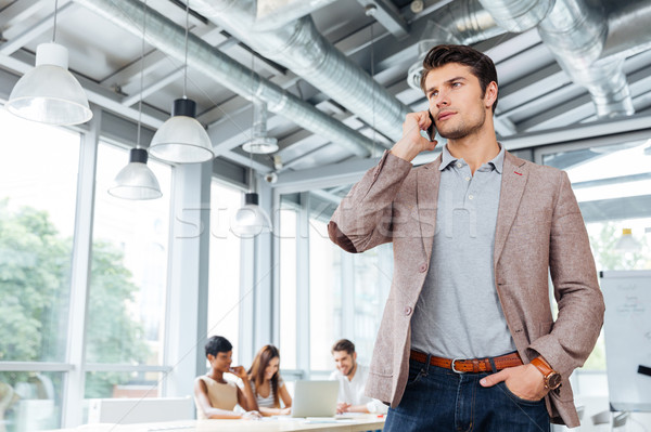 Serious businessman standing and talking on mobile phone in office Stock photo © deandrobot