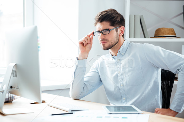 Pensive young handsome businessman in eyeglasses looking at computer monitor Stock photo © deandrobot